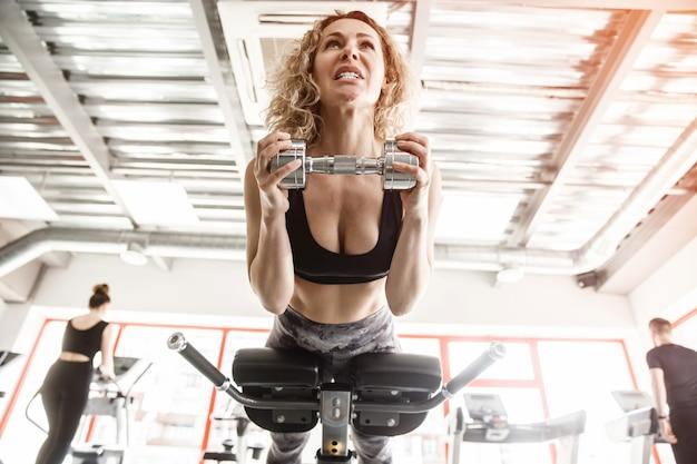 女性がトレーニング器具の上に横たわっています。彼女はダンベルを持っています。