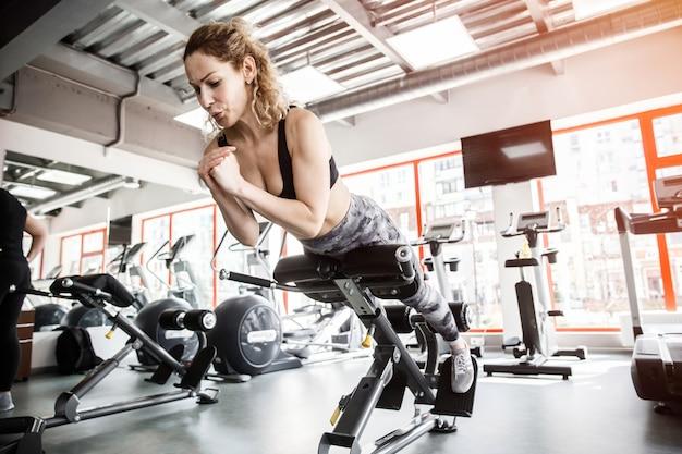 女性がトレーニング器具の上に横たわっています。彼女は腹筋を鍛えています。