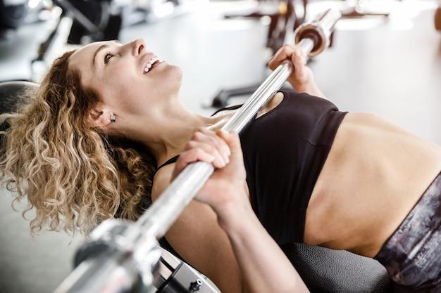 女性がバーベルを手にトレーニング器具の上に横たわっています。彼女は笑っている。