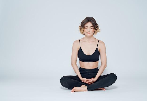 女性は床に足を組んで軽い壁で瞑想しています。
