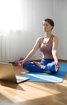 Женщина медитирует в интернете на ноутбуке. концепция йоги видеоконференций.