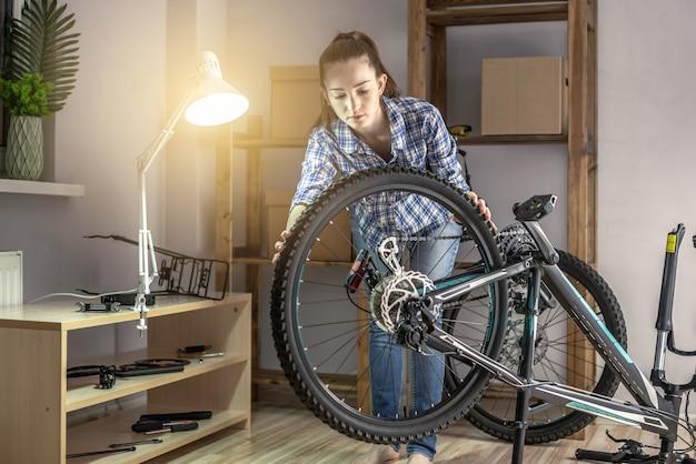 한 여성이 산악 자전거를 정비하고 있습니다. 새 시즌을 위한 자전거 고정 및 준비의 개념