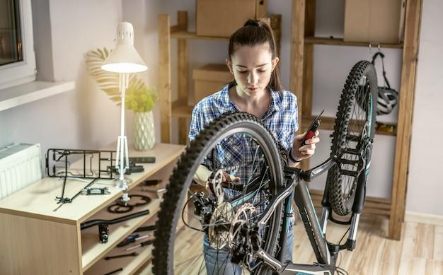 한 여성이 그의 산악 자전거에서 유지 보수를 수행하고 있습니다. 새 시즌을 위한 자전거 고정 및 준비의 개념