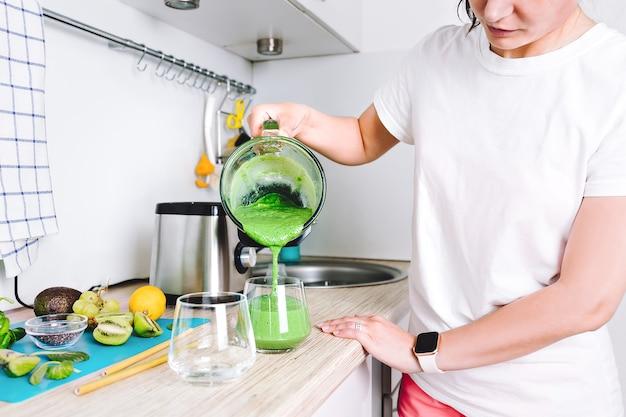 한 여성이 믹서기에 홈메이드 디톡스 주스나 농축 비타민 스무디를 준비하고 있습니다. 건강한 생활 방식, 건강한 스포츠 영양.