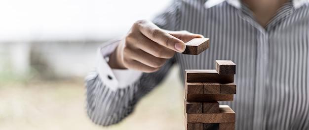 女性は、良いビジネスを営んで問題を解決するように、一列から木のブロックを引っ張っていて、それを壊していません。リスクに関する経営管理の概念。