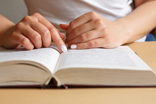 女性が本を読んでいます。手は本を持っています。美しいマニキュア。学生が教科書を勉強しています。情報の教育と研究の概念