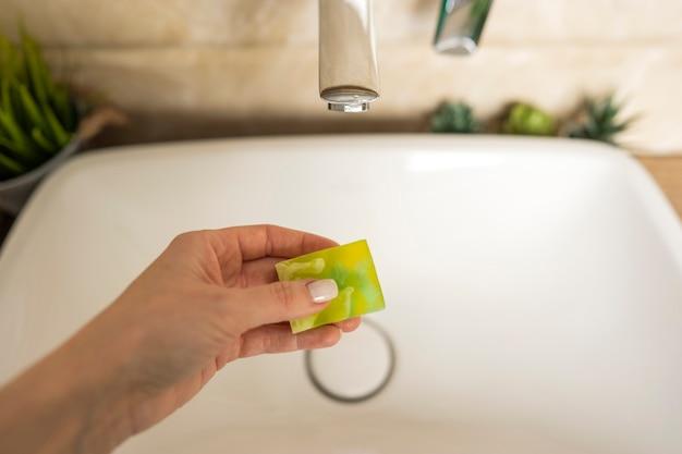 女性は黄色い香りのカモミール石鹸で手を洗う準備ができています