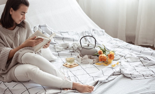 Женщина отдыхает в постели с чаем, книгой и букетом тюльпанов. весеннее утро и концепция выходных.