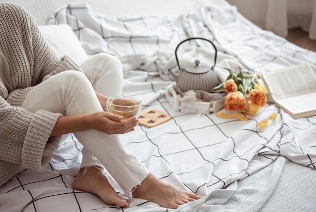 한 여자가 차, 책, 튤립 꽃다발을 들고 침대에서 쉬고 있습니다. 봄 아침과 주말 개념.