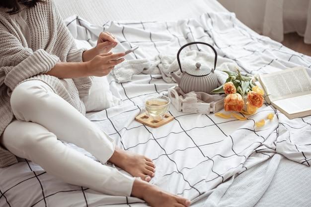 女性はお茶、本、チューリップの花束と一緒にベッドで休んでいます