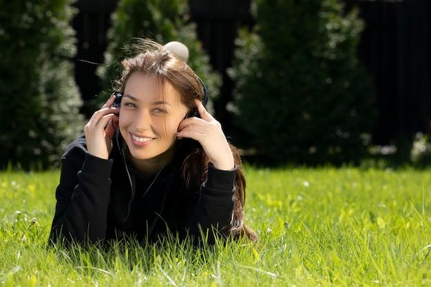 緑の芝生に横になってヘッドホンで音楽を聴いている女性。芝生の概念に頼る。緑の芝生でリラックス。暖かい晴れた夏の日。