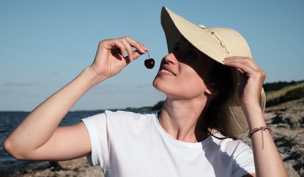 晴天のビーチで休んでいる女性とさくらんぼを食べている女性