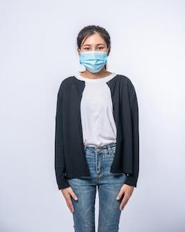 Женщина больна, стоя в маске. наденьте черное пальто и джинсы.