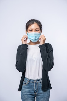 女性はマスクをかぶって病気で立っています。黒いコートとジーンズを着用してください。