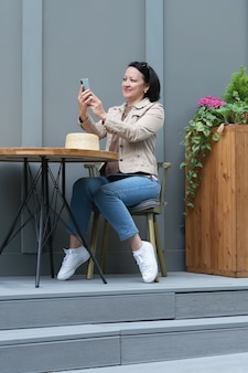 女性が携帯電話を手にカフェのテーブルに座って、ビデオリンクを介して話している。