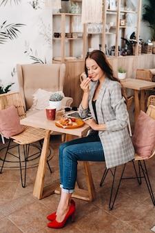 女性がカフェに座ってイチゴを食べています。コーヒーショップで手にイチゴを持った女の子。