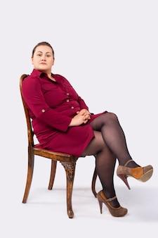 한 여성이 큰 회색 배경의 빨간 드레스 신발 옷을 입고 똑똑해 보이는 의자에 앉아 있다