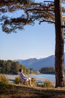 Женщина сидит на раскладном стуле на берегу горной реки в хороший теплый день под большим деревом. спокойное и тихое место для отдыха и размышлений. снаряжение и туристический отдых.