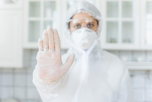 한 여성이 집에있는 부엌 테이블에 앉아 정지 신호를 표시하고 있습니다. 소독제 가정 용품과 가구가있는 보호 복을 입은 사람들 건물 집 소독 코로나 바이러스 또는 covid