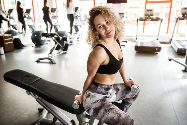 女性がトレーニング器具に座っています。彼女は目をそらして笑っています。