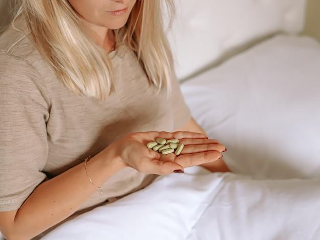 タブレットを手に持ってベッドに座っている女性。