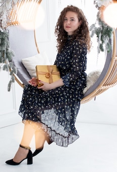 한 여자가 축제의 새해 방에 선물을 들고 앉아 있습니다. 아름다운 조명