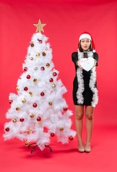 クリスマスツリーの横に女性が立っています