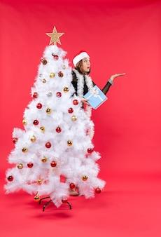 한 여자가 크리스마스 트리 옆에 서 있다
