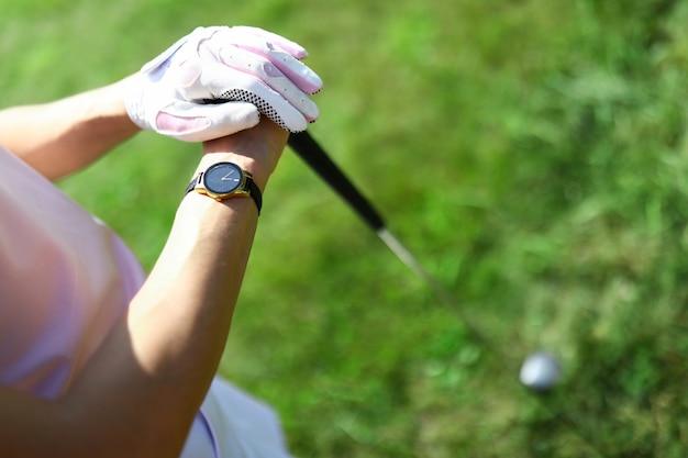 한 여자가 골프 코스에 서서 골프 클럽 권위있는 프로 스포츠를 들고 있습니다.