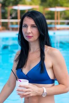 Женщина загорает в бассейне с коктейлем. летние каникулы на пляже портрет