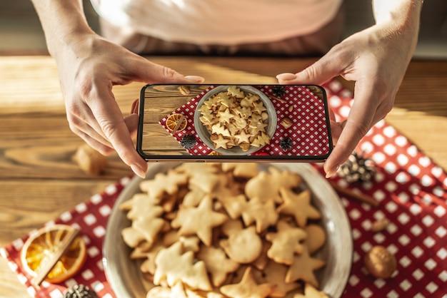 女性は彼女の携帯電話のカメラでおいしい自家製フィギュアホリデークッキーとプレートを写真を撮っています