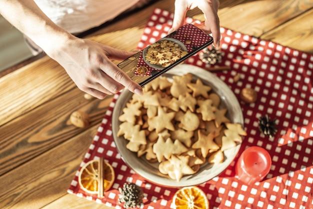 Женщина фотографирует тарелку с вкусным домашним праздничным печеньем с фигуркой на камеру своего телефона