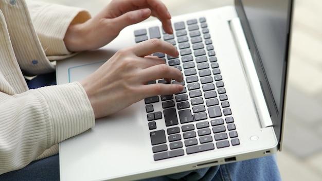 한 여자가 노트북 키보드 클로즈업에 텍스트를 입력하고 있습니다. 여성의 손이 키보드에 입력하고 있습니다. 비즈니스 및 사무실 작업 개념입니다. 4k uhd