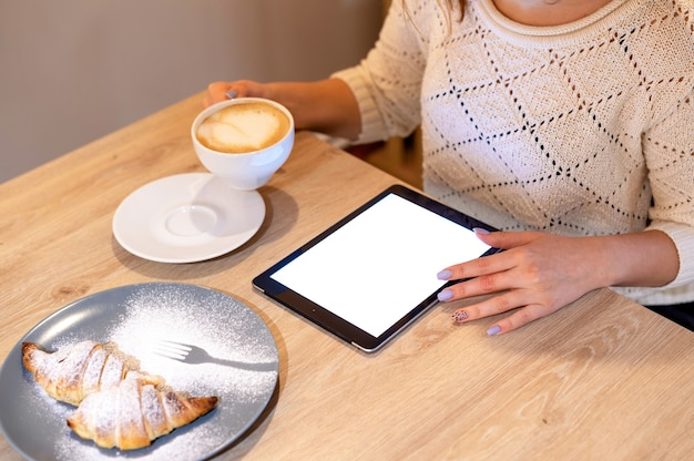 여자는 나무 테이블에 커피 한잔, 디저트를 들고 태블릿을 사용하고 있습니다