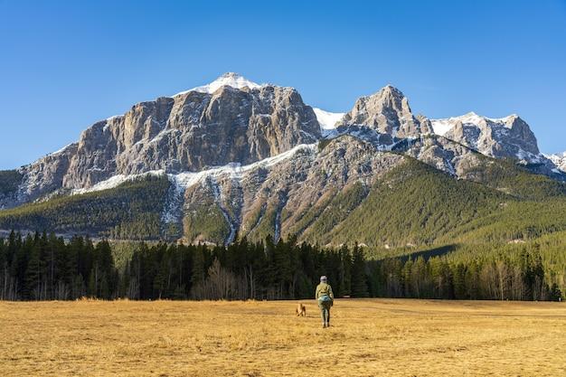 Женщина гуляет с собакой в парке карьер-лейк поздней осенью.