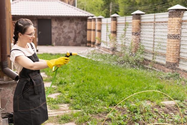 한 여자가 뒤뜰 정원에서 묘목에 물을 주고 있다