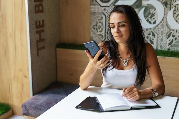 カフェに座って友達とオンラインチャットをしながらビデオコミュニケーションの話をしている女性...