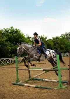 日没時のジャンプ競技で、女性騎手が馬の壁を飛び越えます。若い女の子のライダーは、サドルに乗って馬に乗る。