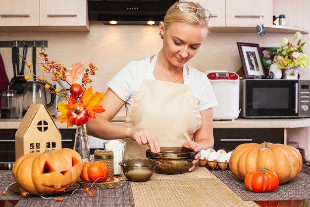 한 여자가 가 장식으로 부엌에서 할로윈을 위한 쿠키 반죽을 반죽합니다. 아늑한 집과 할로윈을 위한 준비입니다. 할로윈을 위한 쿠키 만들기.