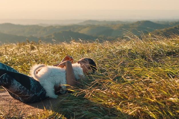 잔디에 누워 운동 후 그녀의 강아지를 포옹하는 여자