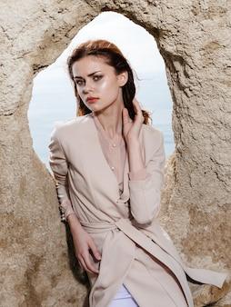 薄着で屋外の岩の穴に寄りかかった女性