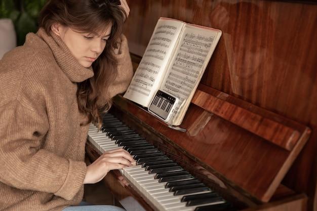 휴대전화의 애플리케이션을 사용하여 피아노 연주를 배우는 여성