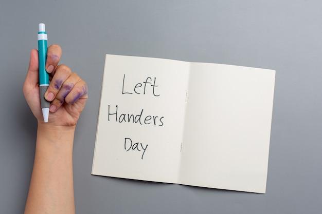펜으로 왼손 여자. 왼손잡이 하루 개념입니다. 무료 사진