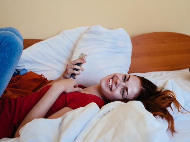電話を手にした女性がベッドに横になり、コミュニケーションの快適さを休む