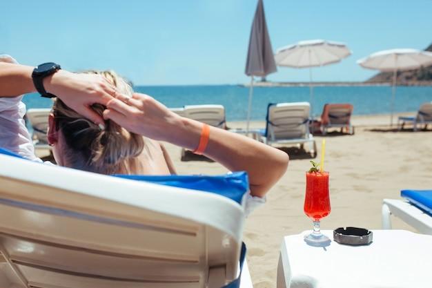 Женщина лежит на шезлонге и смотрит на море и в руках коктейль.