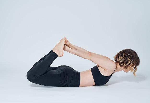 女性がお腹に横になり、つま先に触れる体操ヨガアーサナ