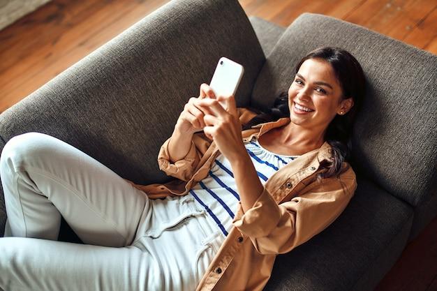女性が居間に電話を持ってソファに横になっている。コミュニケーション、オンラインショッピング。スマートフォンを持った女性がコミュニケーションを取り、休憩し、楽しんでいます。