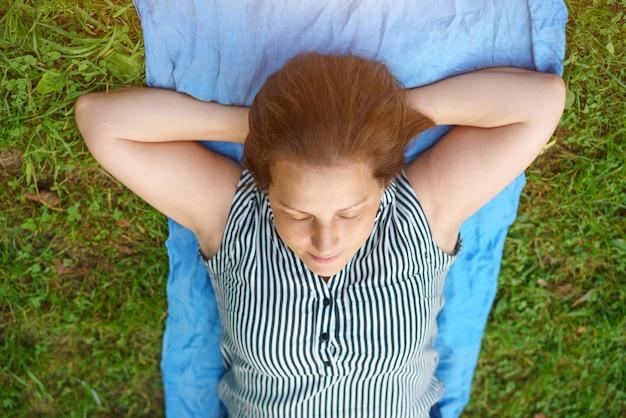 女性は目を閉じて、リラックスして草の上に横たわっています