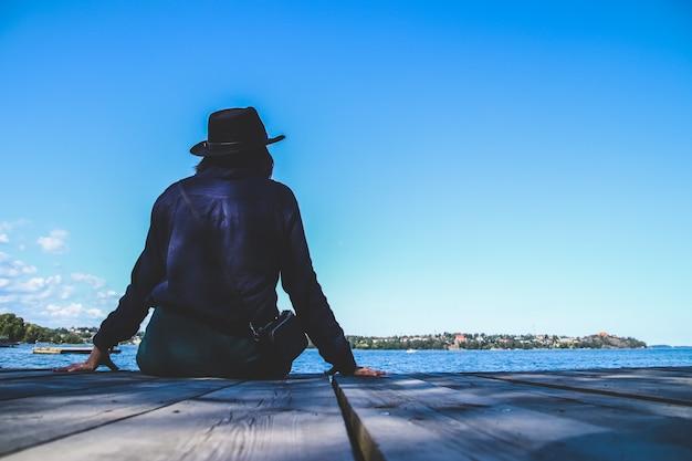 푸른 하늘과 바다에서 목재 부두에 앉아 외로운 여자