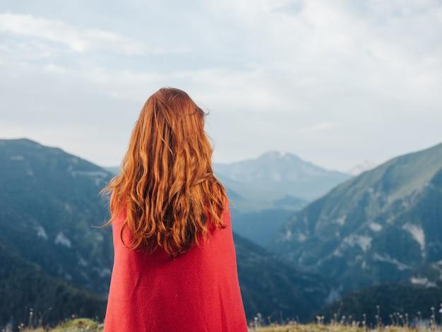 女性は自然の山々と肩に赤い格子縞を見ています。高品質の写真